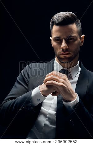 Handsome Thoughtful Man In Black Suit On Dark Background. Man Beauty
