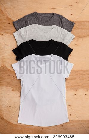Stack Of Different Coloured Womens T-shirt On Wooden Background. Vertical Wiev.
