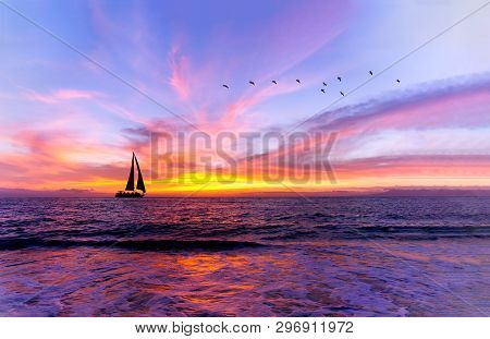 Ocean Sunset Sailboat Is A Vibrant Ocean Sunset With A Sailboat Sailing Along The Water With A Flock