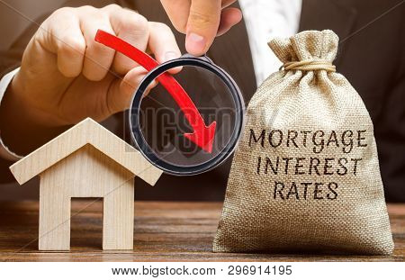 Bag With The Money And The Word Mortgage Interest Rates And Arrow Down And House. Low Interest In Mo