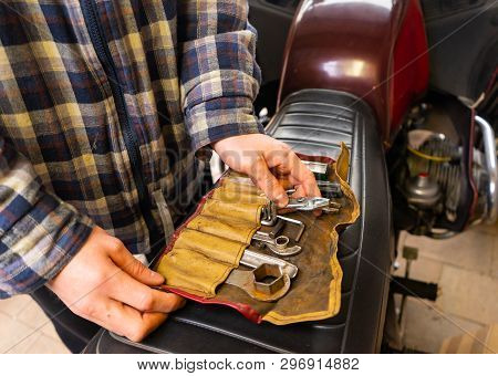 Man With Set Of Tools On Motorcycle Seat