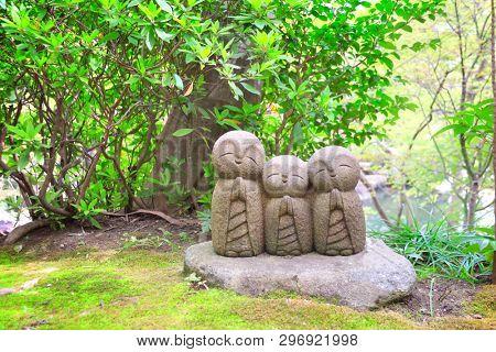 Stone statue of three smiling Jizo (Jizo Bosatsu), Hasedera temple, Kamakura, Japan
