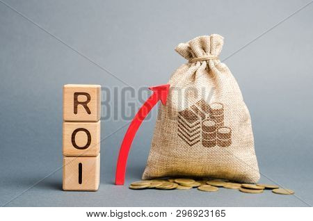 poster of Wooden blocks with the word ROI and the up arrow with the money bag. High level of business profitability. Return on investment, invested capital, rate. Success. Growth. Profitability. Analytics.