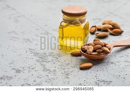Bottle Of Almond Oil And Wooden Spoon With Almonds On Concrete Background, Copy Space. Almond Oil He