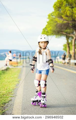 A Little Caucasian Girl Beginner Roller On The Seaboard. Rollerblading And Outdoor Activity Concept