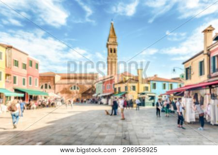 Defocused Background Of Tourists Walking On The Main Square Of Burano Island, Venice, Italy. Intenti