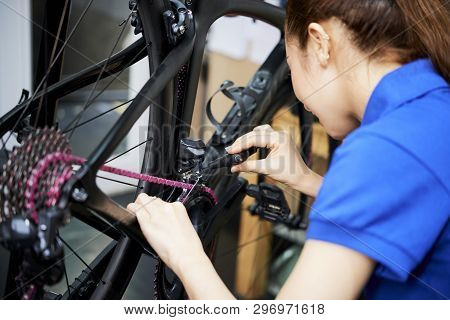 Young Saleswoman Repairing Or Making Setting Of The Bicycle Before The Sale In The Shop