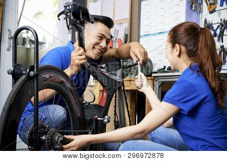 Smiling Asian Mechanic Repairing The Bicycle Together With His Female Assistant In Workshop