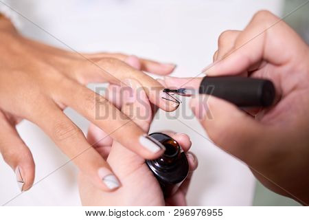 Close-up Of Unrecognizable Professional Manicurist Applying Clear Gel Lacquer On Fingernail While Fi