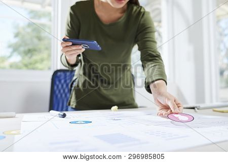 Close-up Of Busy Woman Designer Standing At Table And Putting Sticker To Sketch While Working On Int