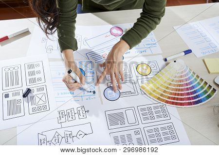 Directly Above View Of Unrecognizable Woman Standing At Desk And Making Notes On Sketch Of App Inter