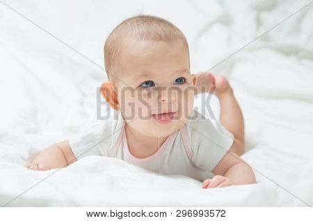 Increased Salivation In The Infant During Teething. A Baby Girl In White Clothes Is Lying On A White