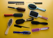 Various colored brushs and combs for hair on yellow background. Set of brush and hairbrush poster