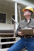 A man in a hard hat standing in front of an old rundown house holding a clipboard in his hand. poster