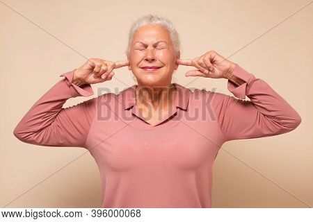 Angry Annoyed Senior Woman Plugging Her Ears To Avoid Loud Noise
