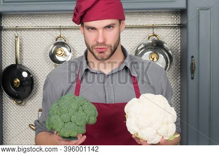 Man Chef In Red Hat, Apron Hold Cauliflower And Broccoli Vegetable In Kitchen. Vegetarian, Health, D