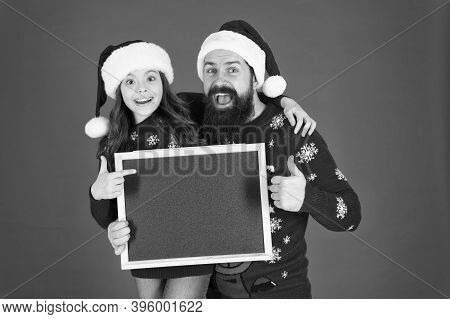 Best Product To Sell At Christmas. Happy Family Presenting Product At Empty Blackboard. Bearded Man
