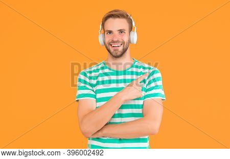 Product For Music Production. Happy Man Point Finger Yellow Background. Product Promotion. Product A