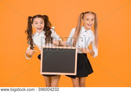 Lesson Ideas. Happy Small Schoolchildren Pointing At Lesson Plan On Blackboard On Yellow Background.