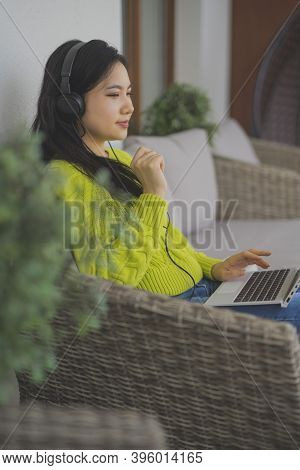 Young Asian Woman Listening To The Music From The Laptop Using Headphones. High Quality Photo
