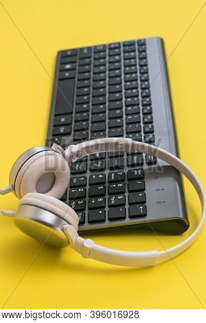 Classic Wireless Keyboard And White Headphones On A Yellow Background. Peripheral Devices For The Co