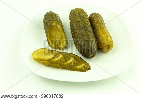 Canned Cucumbers In A Plate On A White Background. Pickled And Crunchy Cucumbers, Delicious Pickled