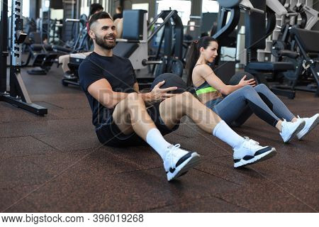 Sport Young People Sitting On A Gym Floor Working Out Together With A Medicine Ball During An Abdomi