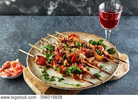 Japanese Style Yakitori Shashlik On A Wooden Board With A Glass Of Red Wine And Ginger.