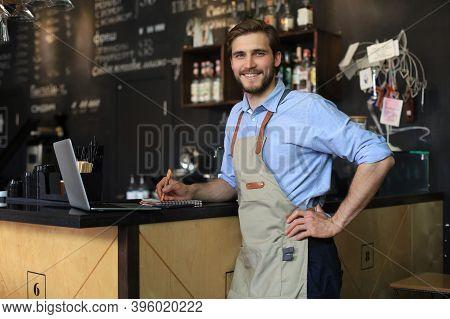 Small Business Owner Working At His Cafe.