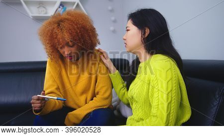 Disappointed Lesbian Couple Looking At Negative Pregnancy Test. Unsuccessful In Vitro Fertilization.