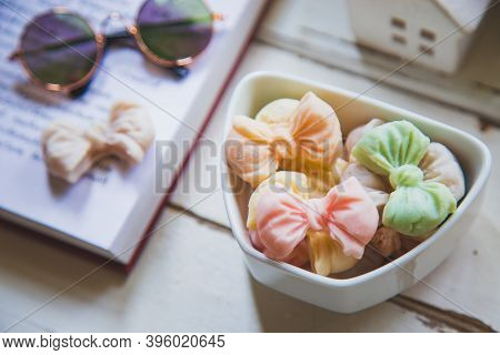 High Angle Views Allure Thai Candy In A Mini Bowl On A Rustic Wooden Table With An Open Book, Allure