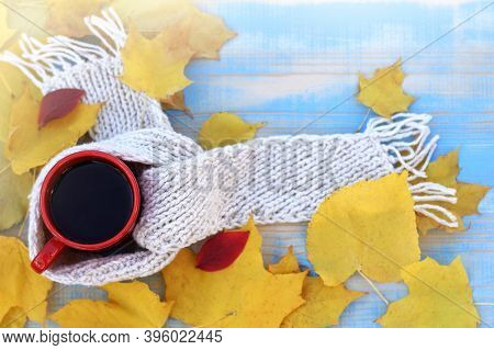 Coffee In A Red Mug With A White Scarf In Yellow Leaves On A Blue Table Top View. Atmosphere Of Warm