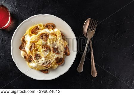 Pappardelle Pasta With Mushrooms, Creamy Sauce And Grated Parmesan Cheese, Shot From Above On A Blac