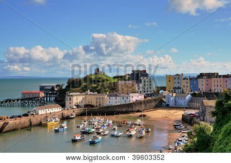 Picturesque view of boats in Tenby Harbour, with its clusters of colourful painted houses, and Castle Hill poster