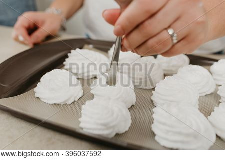 А Photo Of The Hands Of A Woman Who Is Creating With A Spoon A Form Of Meringues On A Tray. A Girl I