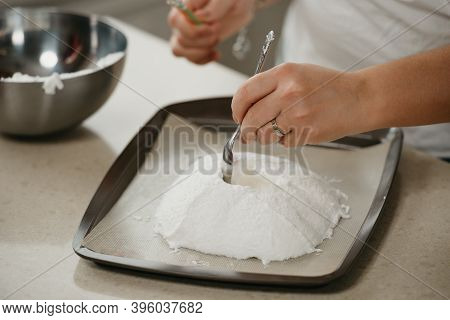А Close Photo Of The Hands Of A Young Woman Who Is Creating With A Spoon A Form Of A Giant Meringue
