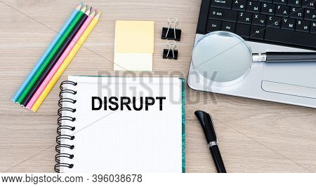 Text Disrupt On An Open Notebook On An Office Table, Next To A Laptop, A Pen, A Magnifying Glass.