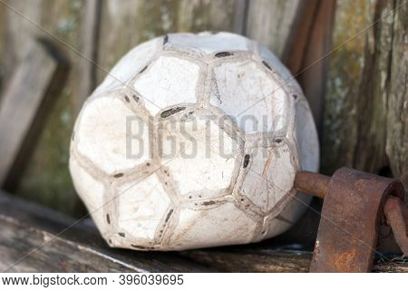 An Old Deflated Soccer Ball Is Lying Idle On The Floor.