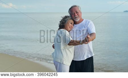 Asian Senior Love Couple Travel On The Beach. Retirement Age Family Relaxing And Recreation On Summe