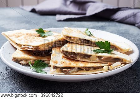 Pieces Of Quesadilla With Mushrooms Sour Cream And Cheese On A Plate With Parsley Leaves. Concrete B