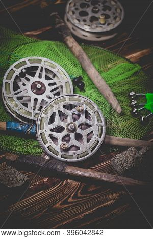 Old Rarity Bottom Fishing Reels On A Wooden Background. Bell, Fish Tank And Makuha Cubes. Studio Pho