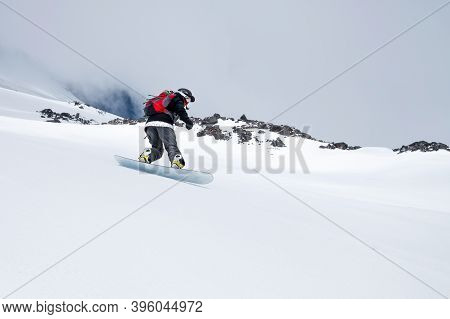 Woman Snowboarder Has Fun Riding On Snowy Off-road Freeride In The Italian Alps. Professional Sports
