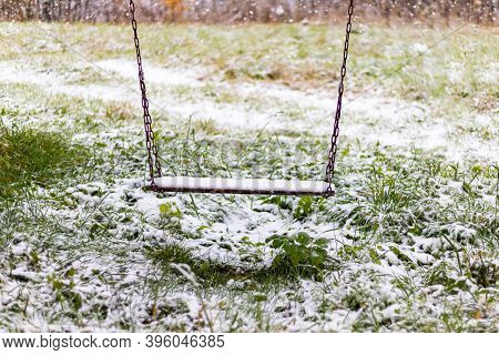 Homemade Wooden Swing Covered First Snow At Winter On Natural Background. Loneliness, Solitude Conce