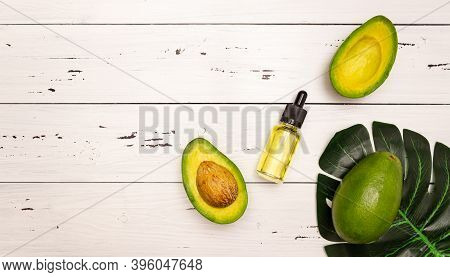 Avocado Oil In A Glass Bottle With A Pipette, Avocado Cut. Cosmetics For Body, Face, Skin And Hair C