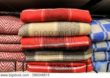A Stack Of Warm Soft, Wool Plaids In A Cage Lies On A Shelf In A Wardrobe, Store. Blankets For Warmt