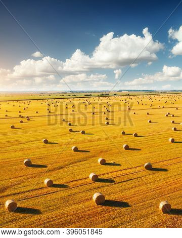 Attractive view from a drone flying over the rural area and hay-roll on field. Location place of Ukrainian agrarian region, Europe. Picturesque nature photography. Discover the beauty of earth.