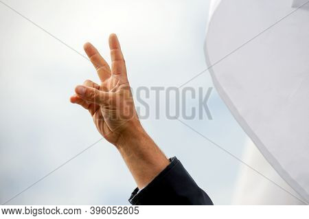 Details With The Hand Of A Protestor Showing The Victory Sign During A Political Rally.
