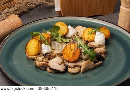 Fried Porcini Mushrooms With New Potatoes Garnished With Arugula