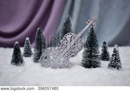 Winter Composition Violin Among Snow-covered Trees In Deep Snow On A Lilac-gray Background