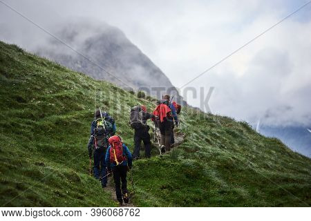 Back View Of Tourists With Backpacks Using Trekking Poles While Climbing The Grassy Hill. Group Of A